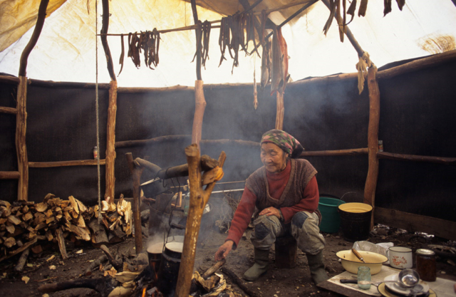 Koryak woman by the fire in her tent, Kamchatka